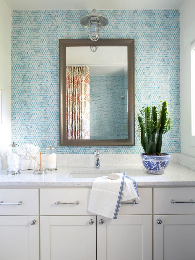 Bathroom Blue tiles. A handsome framed mirror creates a focal point behind the vanity, and contrast for the surrounding blue tiles and white ceiling and walls.