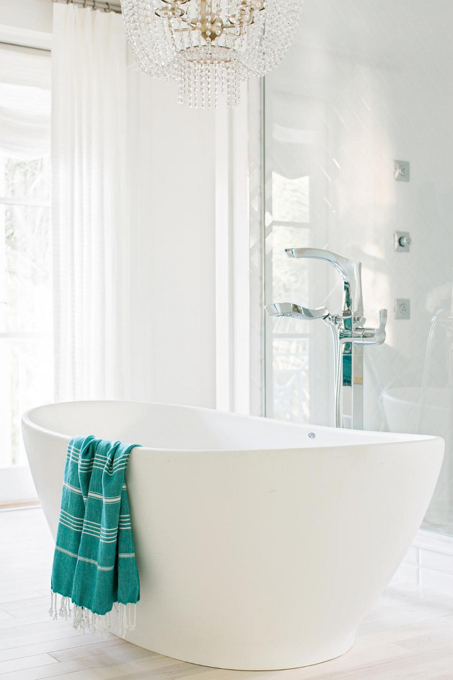Bathtub. Made of engineered molded stone, the deep tub sits like an elegant piece of furniture in the center of the room.