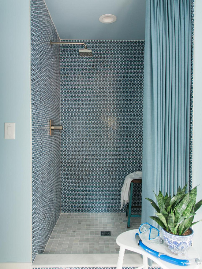Cobalt blue penny round tiles with contrasting white grout lines the interior of the shower. It lends a beachy feel to the room and pairs well with the French blue painted walls of the space.