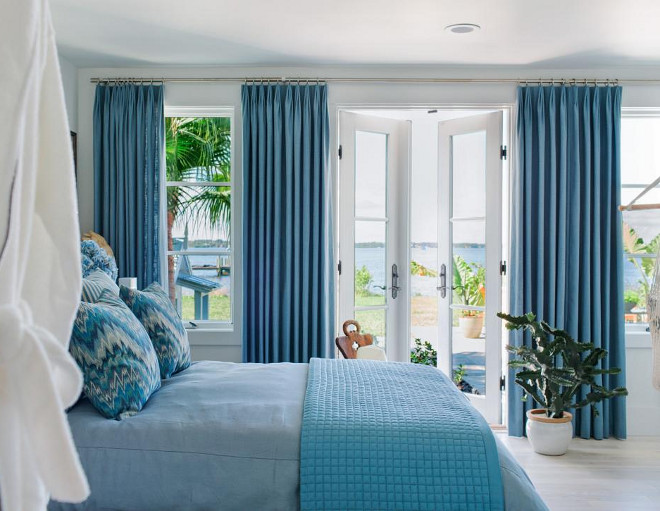 This bedroom suite has French doors that open out on to a terrace. The blue-gray linen draperies frame the view of the yard and nearby river.