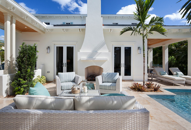 Outdoor lounge area and fireplace with white wicker furniture. #Outdoors #loungearea #fireplace Casatopia, LLC - Ibi Designs