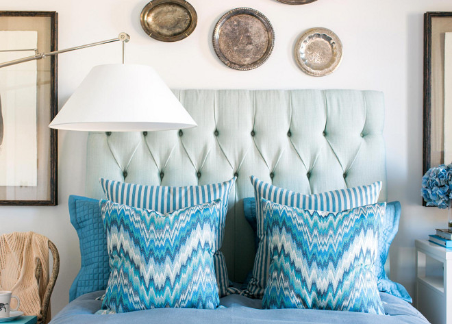 The soft white walls, ceiling and trim is the perfect back drop for the sea foam green, linen tufted headboard. Pops of bold color stand out in the classic flame stitch and ticking stripe pillows.