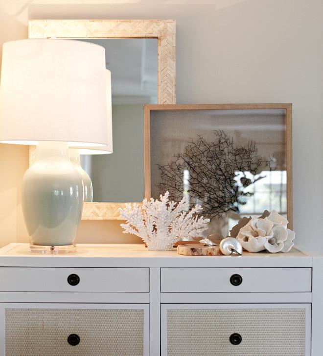White dresser with coastal vignette. White dresser with coastal decor - vignette. White dresser with coastal decor, inlaid bone mirror, grass cloth, coral art, seashell, sea glass, sea foam green.