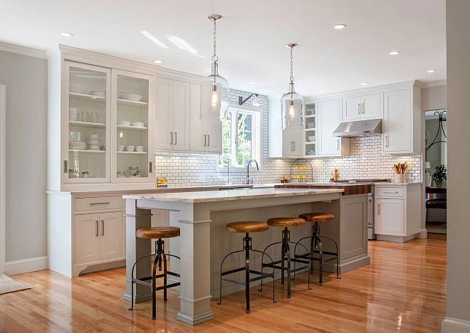 White kitchen with gray island paint color. The white kitchen cabinet paint color is called Cottonball, from Pennville Custom Cabinetry. The gray island paint color is Benjamin Moore Fieldstone. #Whitegraykitchenpaintcolor #Grayislandpaintcolor #BenjaminMooreFieldstone Pennville Custom Cabinetry