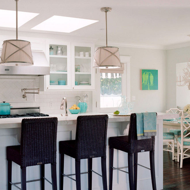 White and turquoise kitchen, Lovely airy beachy coastal kitchen design with soft gray walls, chrome pleated drum pendant island lights, black seagrass barstools, white kitchen cabinets, subway tiles, white faux bamboo dining chairs, turquoise blue striped chair cushions, white chandelier and turquoise blue accents #Kitchen #BeachhouseKitchen #CoastalKitchen #WhiteandturquoiseKitchen Waterleaf Interiors