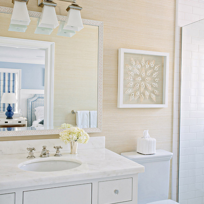 Neutral bathroom features walls clad in tan grasscloth lined with a white washstand with inset drawers topped with white marble nder a mosaic mirror and a 3 light sconce, Triple Chinoiserie Bath Light in Polished Nickel #NeutralBathroom #Bathroom #Grasscloth Waterleaf Interiors