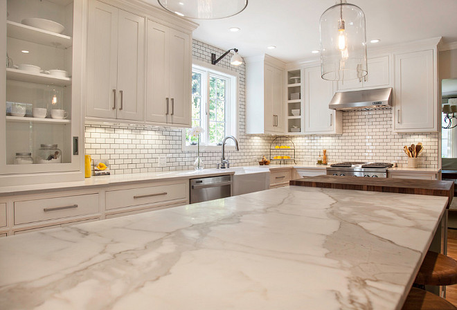 Off-white kitchen with honed Calacatta gold marble countertop. #Offwhitekitchen #OffwhitekitchenCountertop #OffwhitekitchenhonedCalacattagoldmarblecountertop #honedCalacattagoldmarblecountertop New England Design Works