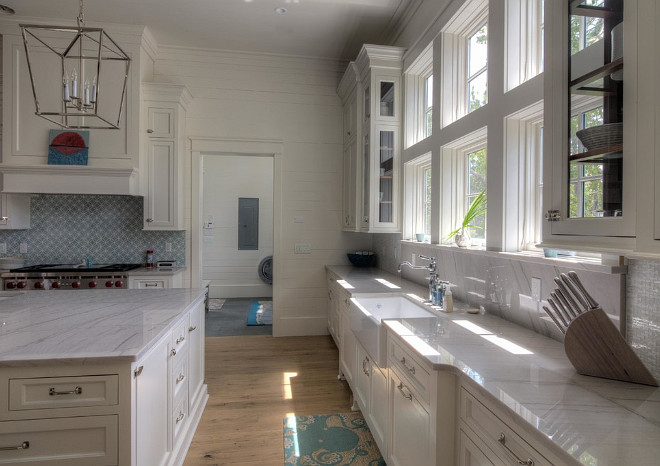 Kitchen with white shiplap walls, beached white plank floors, white marble countertops and blue and white mosaic tile backsplash. 30A Interiors