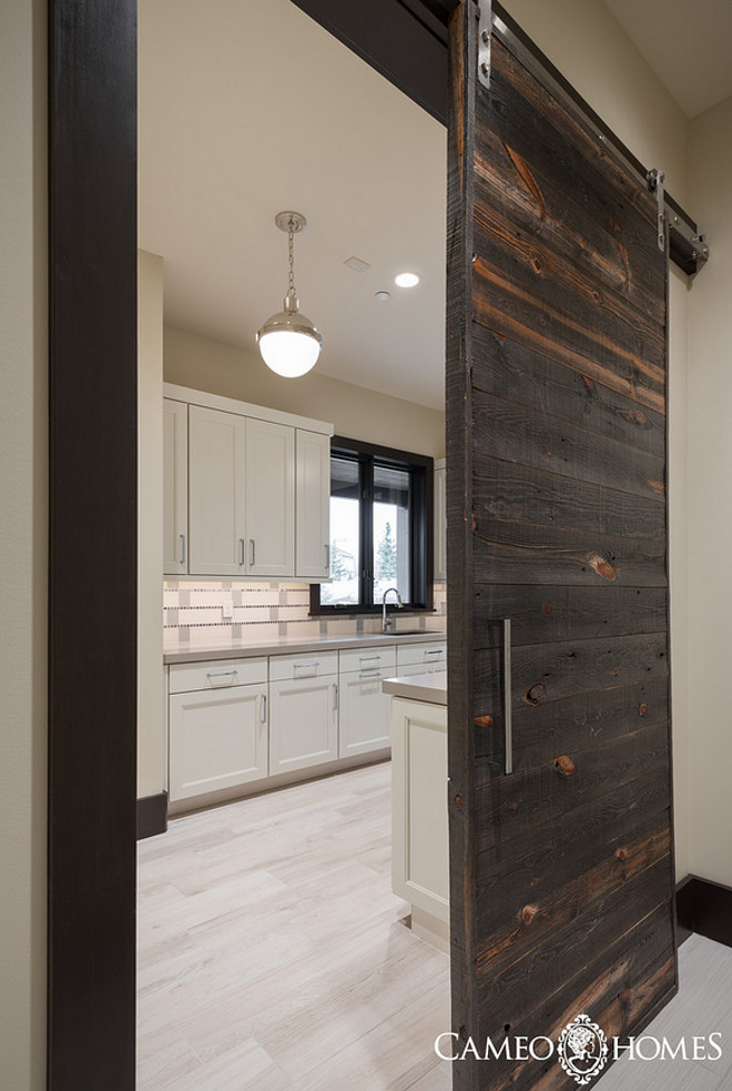 Laundry Room with a sliding barn door made of reclaimed wood. Laundry Room with a sliding barn door made of reclaimed wood ideas. #LaundryRoom #slidingbarndoor #reclaimedwooddoor Cameo Homes Inc.