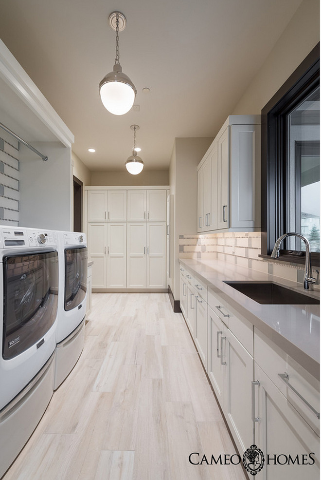 Laundry room with white cabinets, gray quartz countertop, wood grain ceramic tiles and walls painted in Pale Oak by Benjamin Moore. Laundry Room #Laundryroom Cameo Homes Inc.