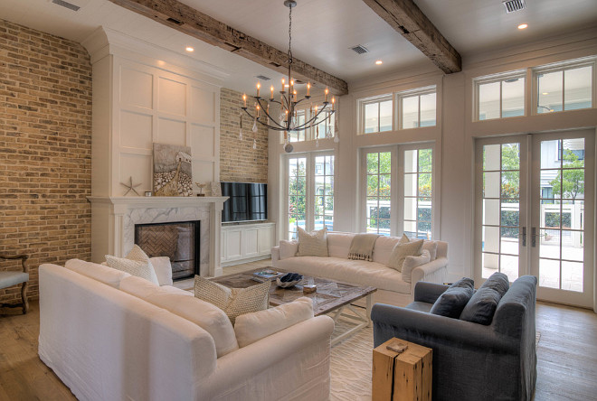Living room with fireplace, reclaimed brick wall, reclaimed wood beams, bleached wide plank floors and French doors with transoms. #livingroom