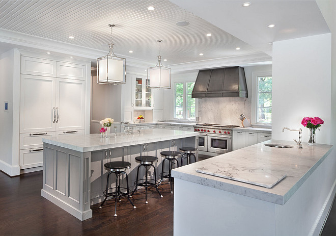 Kitchen with crisp white cabinets, zinc hood, gray island with marble countertop and separate peninsula with prep sink. Nahra Design Group