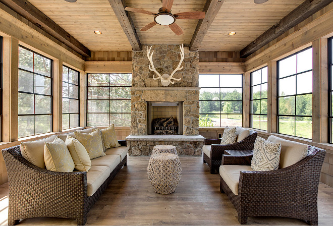This rustic sunroom features reclaimed wood floors, reclaimed wood beams, black metal window frames and a fieldstone fireplace, Rustic Sunroom with outdoor stone fireplace antler decor Indoor Ceiling Fan recessed lighting wicker furniture wood ceiling wood walls