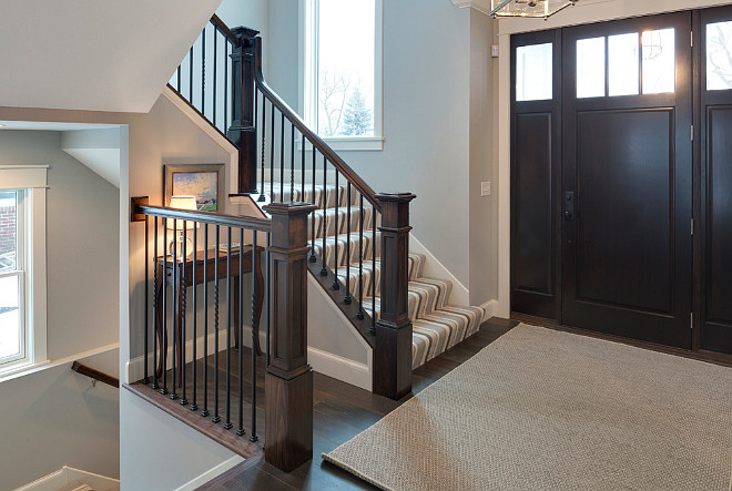 Front entry foyer with dark stained wood door, dark stained hardwood floors, dark stained staircase railing and newel post. Grace Hill Design