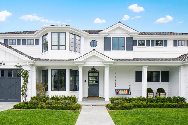 Home Exterior barn door batten shutters bay windows beach house blue accents blue trim front porch hedges landscaping porch swing shingle roof square column posts stable door traditional beach style two story home white house #Homeexterior Legacy CDM Inc.