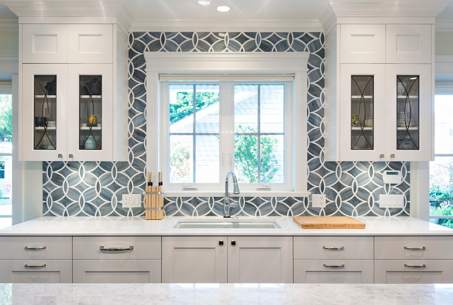 Eclipse glass cabinets. White and blue kitchen boasts white shaker cabinets painted Benjamin Moore White Heron paired with Princess White Quartzite countertops and an Ann Sacks Beau Monde Glass Polly Tiles in Absolute White and Pearl. A kitchen sink, Kohler Frost Blue Sink, with a Brizo Talo Faucet stands under windows flanked by eclipse glass cabinets #eclipseglasscabinets