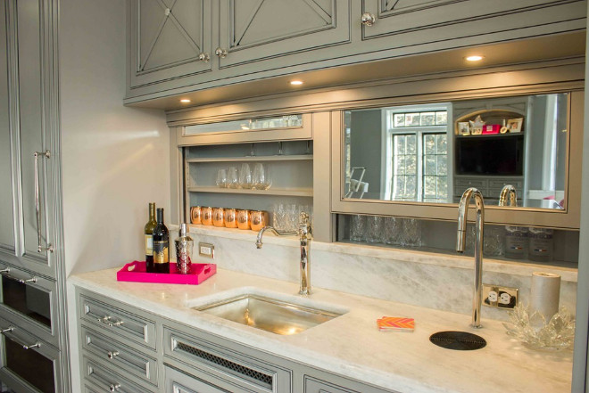 Butlers pantry cabinet door ideas. This kitchen bar has remote-controlled retracting mirrored doors where glassware is stored. Above, a bar sink and a sleek, concealed Top Brewer coffeemaker is placed on an elegant marble countertop.  #Butlerspantry #bar #cabinet #butlerspantrycabinet #Barcabinet #kitchen Lori Wiles Design