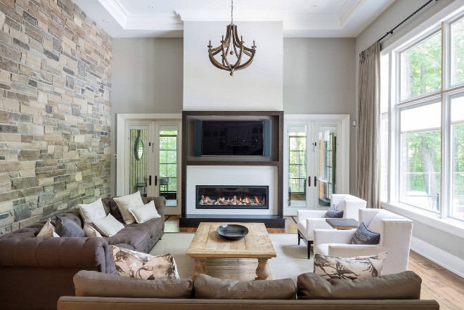 Family Room Stone Wall Ideas. Family Room Stone Wall. Family Room with accent stone wall. Family room features stone wall, tray ceiling, floor to ceiling windows and wood chandelier. #FamilyRoom #StoneWall #Familyroomstonewall David Small Designs