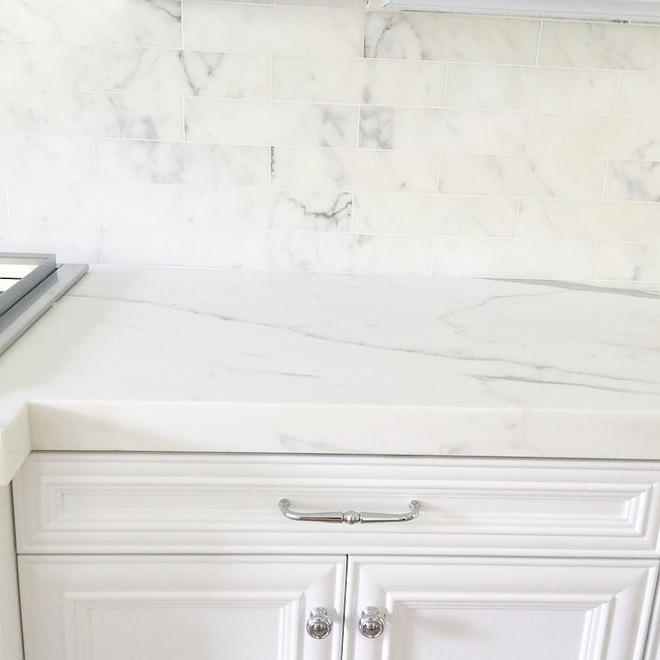 White kitchen cabinets painted in white lacquer with no pigment in it, semi gloss sheen and Calcutta marble, 3″x12″ subway tiles with white grout for the kitchen backsplash. For the island and counters I picked a 2″,honed Calcutta marble with a clean, mitered edge. Restoration Hardware silver pulls and knobs blended well with the cool tones in the marble. #kitchen #marble #backsplash #countertop #knobs #pulls #hardware Becki Owens
