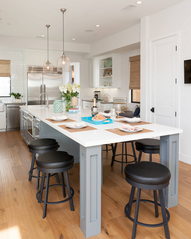 Long gray island with white quartz countertop. Quartz is a relative affordable countertop material and very durable. It's also a good option for long kitchen counters. #Kitchen #QuartzCountertop #Whitequartz #longkitchenislandcountertop Jasmine Roth.