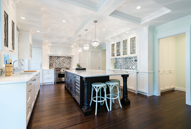 White Kitchen Coffered Ceiling. Cyan Janus Globe Pendants hang over a black kitchen island with turned legs fitted with a Sub Zero Dual Wine Fridge topped with Princess White Quartzite lined with white backless counter stools, Restoration Hardware Madeleine Backless Leather Stools. Fabulous kitchen boasts white shaker cabinets painted Benjamin Moore White Heron paired with Ann Sacks Beau Monde Glass Polly Tiles in Absolute White and Pearl. A kitchen sink stands under windows flanked by eclipse glass cabinets and coffered ceiling. #WhiteKitchenCofferedCeiling #KitchenCofferedCeiling Sarah Gallop Design Inc