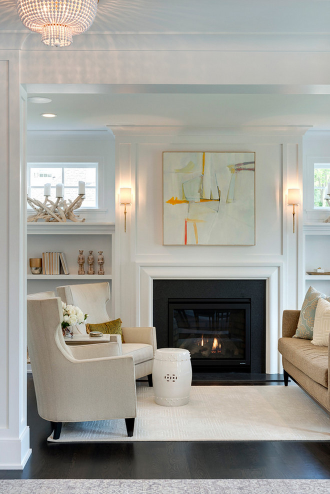 This living room features a gray and orange abstract art piece illuminated by Dauphine Sconces hanging over a white, sleek fireplace adorned with a black slate surround flanked by open built in bookcases under windows. White living room painted in Benjamin Moore OC-117 Simply white featuring neutral furniture and decor. #Livingroom #neutrallivingroom #whitelivingroompaintcolor #BenjaminMooreOC117Simplywhite #neutrallivingroompaintcolor #neutrallivingroomfurniture Spacecrafting Photography. City Homes Design and Build, LLC