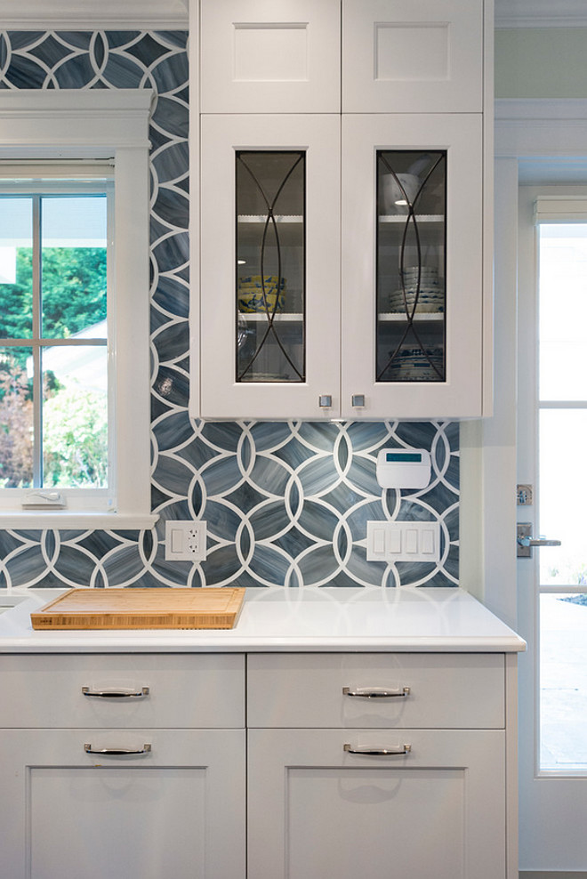 Blue tile backsplash. White and blue kitchen boasts white shaker cabinets painted Benjamin Moore White Heron paired with Princess White Quartzite countertops and an Ann Sacks Beau Monde Glass Polly Tiles in Absolute White and Pearl. A kitchen sink, Kohler Frost Blue Sink, is paired with a Brizo Talo Faucet flanked by glass eclipse cabinets. #Bluetilebacksplash #Bluebacksplash #Bluetile Sarah Gallop Design Inc.