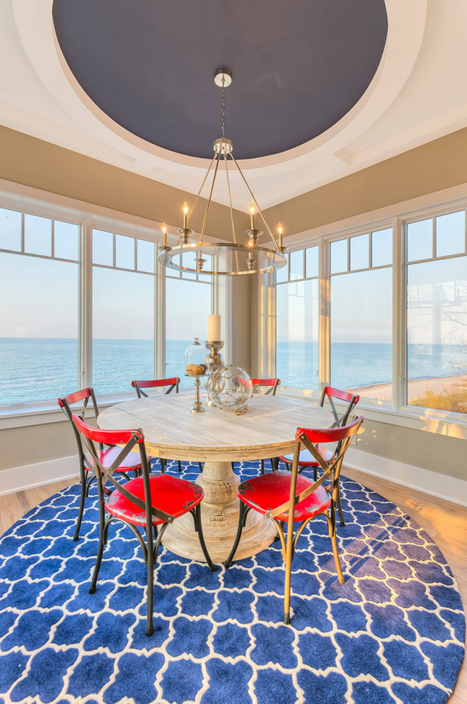 Coastal Dining Room beach front Beachfront Interiors candlesticks classic design distressed red dining chairs lakefront home large windows Nautical Luxuries navy blue ocean view round blue area rug round ceiling design round dining table sunroom water front water view