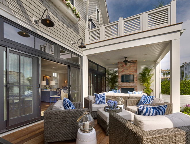 Deck. Sliding patio doors open to an Ipe deck with wicker furniture, outdoor fireplace with outdoor tv and a second floor roof porch with louvered railings. #Deck #Outdoorliving #Ipedeck #Deckideas #Outdoorfireplace #Outdoors Asher Associates Architects. Megan Gorelick Interiors