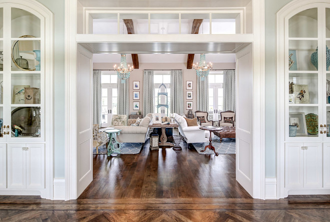 Arched built-in cabinets frame a wide doorway with transoms leading to the formal living room. Artisan Signature Homes.