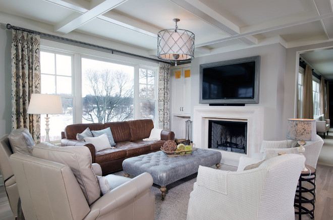 Neutral living room painted in Revere Pewter by Benjamin Moore, Limestone fireplace, whitewashed hardwood floors and lattice drum pendant light. Mike Schaap Builders
