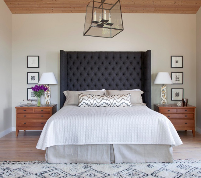 Oversize gray wool tufted headboard adds mass and drama to the master suite. Lamps made from reclaimed antique carved relics, antique Morroccan rug adds texture and warmth. Savant Design Group