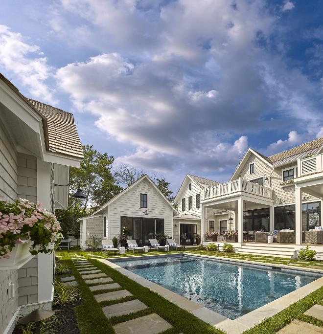 Shingle home backyard. Shingle home pool backyard . Shingle home pool backyard with stone pavers and pool house. #ShingleHome #Backyard #Pool #PoolHouse #StonePavers Asher Associates Architects