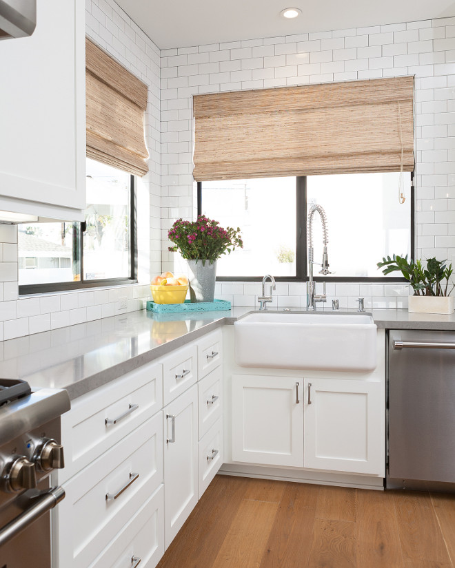 Sleek white kitchen with shaker style cabinet doors, gray quartz countertop and counter to ceiling subway tile. #Shakercabinet #shakerstylecabinet #shakerstylecabinetdoor #kitchenshakerstylecabinet Jasmine Roth.