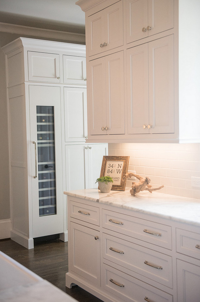 Classic kitchen elements. Kitchen features classic white cabinets, white marble countertop, white subway tile backsplash, polished nickel hardware and dark stained wood floors. Artisan Design Studio
