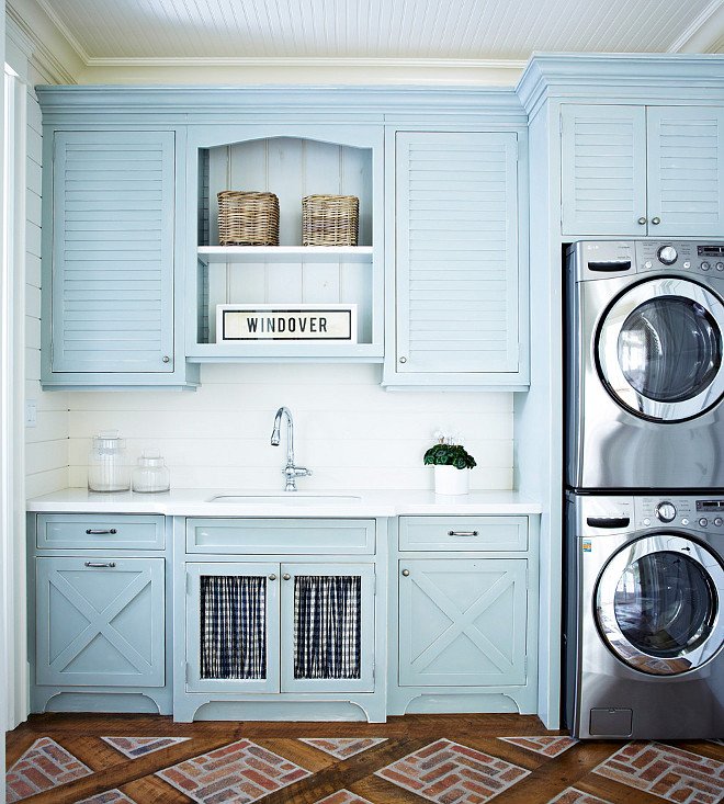 Laundry Room Cabinet Paint Color. Blue Laundry room cabinet paint color. Blue laundry room features a beadboard ceiling over blue louvered upper cabinets and blue x trim lower cabinets paired with white quartz countertops and a shiplap backsplash. A wide laundry room sink is place dover cabinets lined with black and white buffalo check curtains placed under blue beadboard backed shelving next to an enclosed stacked washer and dryer alongside a brick floor. #Bluelaundryroom #laundryroomcabinet #laundryroompaintcolor  Muskoka Living.