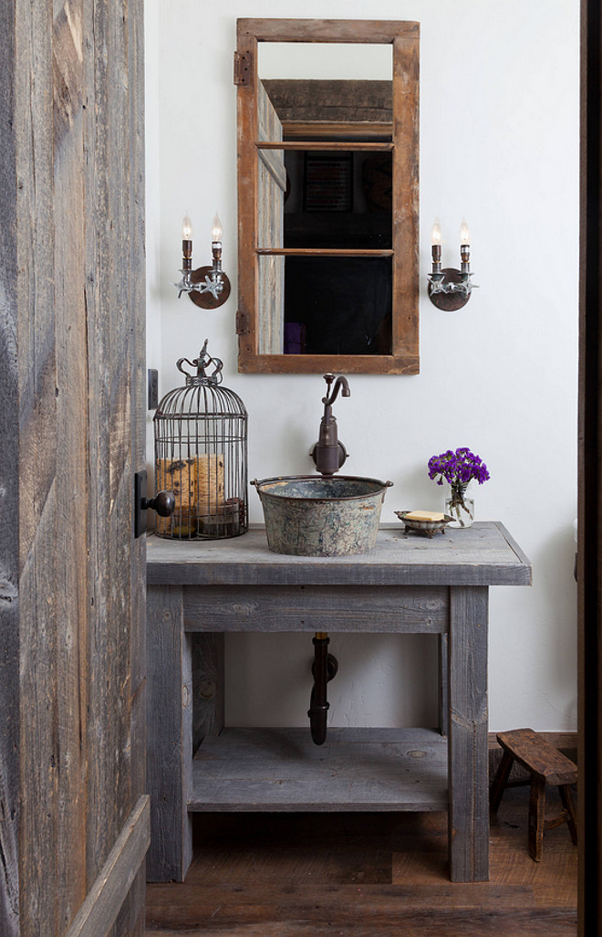 Farmhouse Bathroom. Authentic Farmhouse bathroom with custom vanity made from reclaimed Wyoming snow fence wood is a home for an antique milk bucket fashioned into a sink. The mirror is made from an old window frame, and the light fixtures from old plumbing fittings. Authentic farmhouse interiors. #Farmhousebathroom #bathroom #farmhouse #Farmhouseinteriors #AuthenticFarmhouseInteriors  Dragonfly Designs