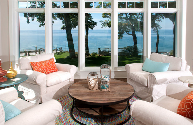 Coastal living room. Lake views can be seen through 8-foot tall windows in the sitting area of the living room. Vivid pops of color appear throughout as seen in this comfy lounging area that provides a perfect spot to watch the sunset over the lake. Coastal homes. Coastal interiors. #coastal #coastalLivingroom #CoastalInteriors #CoastalHomes