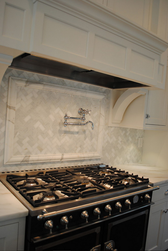 Kitchen backsplash. La Cornue Range, Waterworks pot filler, Custom hood, Backsplash in Honed Carrara Marble in Herringbone, Counters in Honed Imperial Danby. #Kitchen #backsplash  Stacye Love Construction & Design, LLC