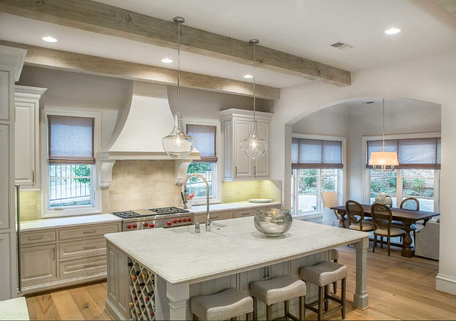French kitchen with graywashed cabinets and island. French kitchen features also whitewashed ceiling beams and seeded glass pendants above island. Pendants above island is Jamie Young Seeded Glass Nimbus 3 Light Chandelier.
