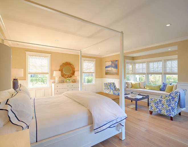 Bedroom. Bedroom features light tan walls, white four poster canopy bed and a charming window seat. #Bedroom.