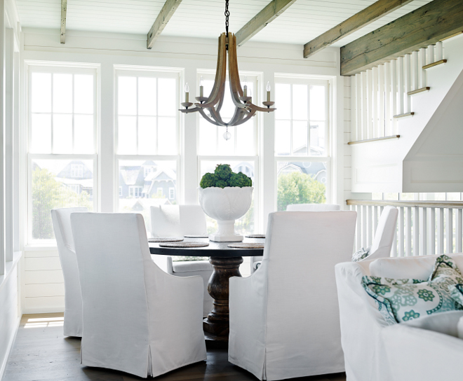 Dining Room Decor Ideas. Coastal inspired dining room. This dining room has everything I love; plenty of natural light, a round table and white slipcovered dining chairs. Chairs are from Lee Industries. Chandelier is Manning 6 Light Chandelier from Arteriors #CoastalDiningRoom #DiningRoom #Coastalinspired #coastalhomes #diningroomdecor #Chandelier #ArteriorsChandelier T.S. Adams Studio, Architects