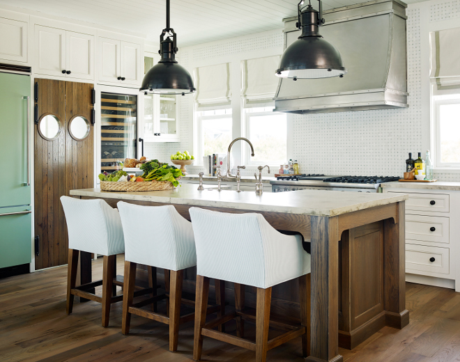Coastal kitchen. This coastal kitchen features plenty of storage, workspace and character. I am loving the walnut stained island and the swing doors with porthole windows. Pendants are Large Country Industrial Pendant from Circa Lighting. #CoastalKitchen #CoastalKitchenlighting #Coastallighting #kitchenpendants #LargeCountryIndustrialPendant #CircaLighting #CircaLightingPendants T.S. Adams Studio, Architects