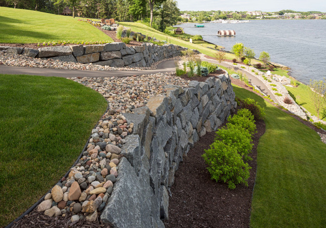 Tiered garden ideas. Tiered garden with retainer walls made of Bluestone. This blue-stone lined trail down to the lake makes for a great walk to the water. The walk is surrounded by beautiful shrubs that offer a variety of seasonal color. #Tieredgarden #retainerwalls #bluestone #retainergardenwall Southview Design