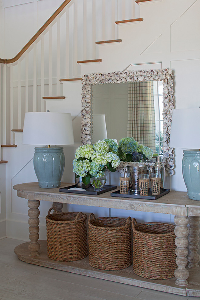 Coastal Foyer with natural elements. This coastal foyer features wainscoted staircase, an oval console table filled with three round woven baskets and topped with watery blue table lamps and a large rectangular seashell encrusted mirror. #CoastalFoyer #Foyer #Foyeswainscotting #Foyerwalls #Foyerpanelledwalls #coastalinteriors Urban Grace Interiors