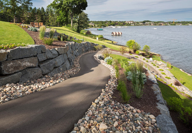 Drop backyard landscaping ideas. The path is wide enough for a golf cart but also makes for beautiful walk down to the lake. The blue-stone wall and variety of perennials and annuals makes for a delightful view for passersby on the lake. Southview Design