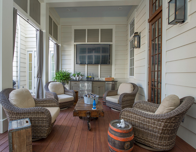 Outdoor Porch with TV. This outdoor porch features a TV and a built-in outdoor kitchen. Countertop – Black Absolute granite honed. Ratana Swivel Chairs. Exterior Lights –The Copper Lighting Co. Custom – Outdoor Draperies. #OurtdoorTV #Porch #TVPorch #outdoorkitchen Interiors by Courtney Dickey and T.S. Adams Studio.