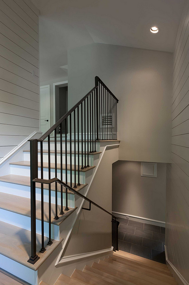 Staircase shiplap walls, white oak hardwood floors with whitewash finish and wrought iron stair balusters and handrail. #staircase #shiplap #wroughtironstairs #balusters #handrail #whiteoakfloor Connie Anderson Photography. Elizabeth Garrett Interiors