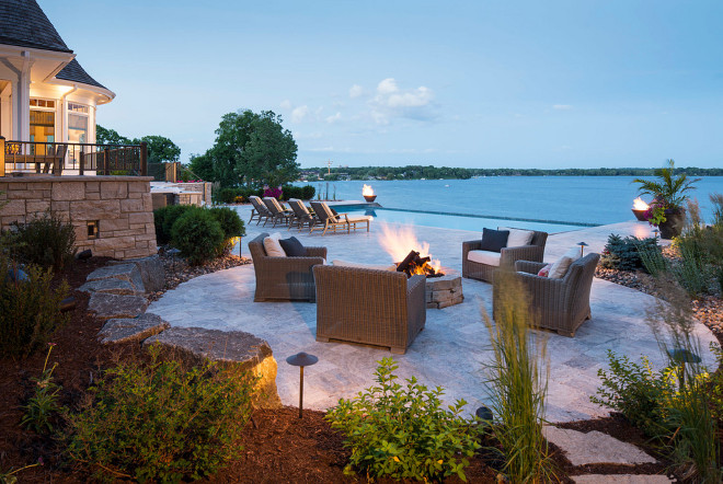 Backyard. There is nothing like a firepit with a view. This lovely firepit overlooks an infinity swimming pool and the firebowls on either side of the pool frame the lake nicely making this area a great place to take in the evening with friends and family. #backyard Southview Design. Eskuche Design.
