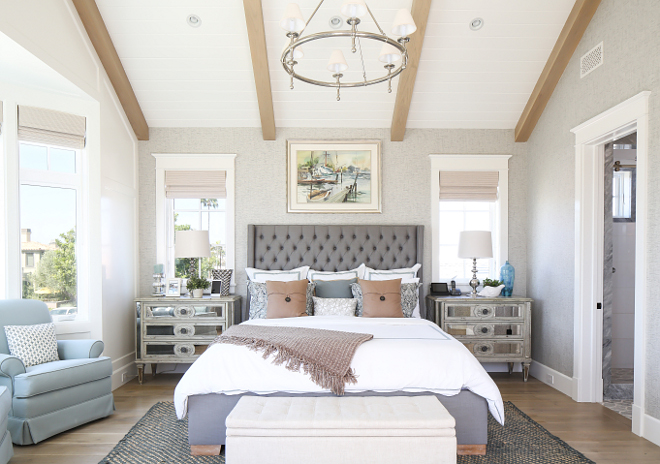 Bedroom. 21. This master bedroom features textured gray wallpaper, vaulted ceilings with exposed beams, light color wood floor and an elegant tufted headboard flanked by mirrored night stands. #bedroom Patterson Custom Homes. Interiors by Trish Steele, Churchill Design.